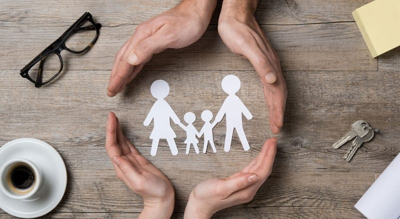 Paper Family Being Protected by Hands