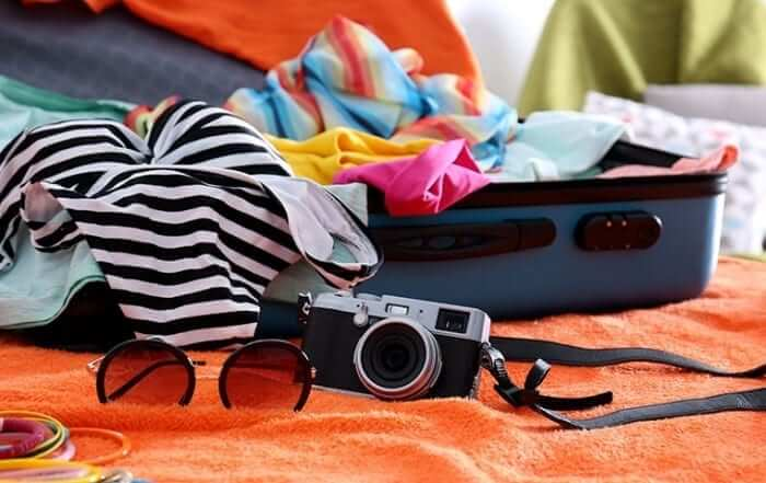 Unpacked suitcase with glasses and camera
