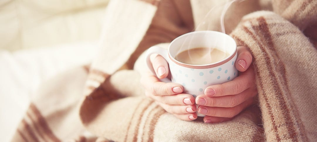 Woman in a blanket sitting with a hot cup of coffee