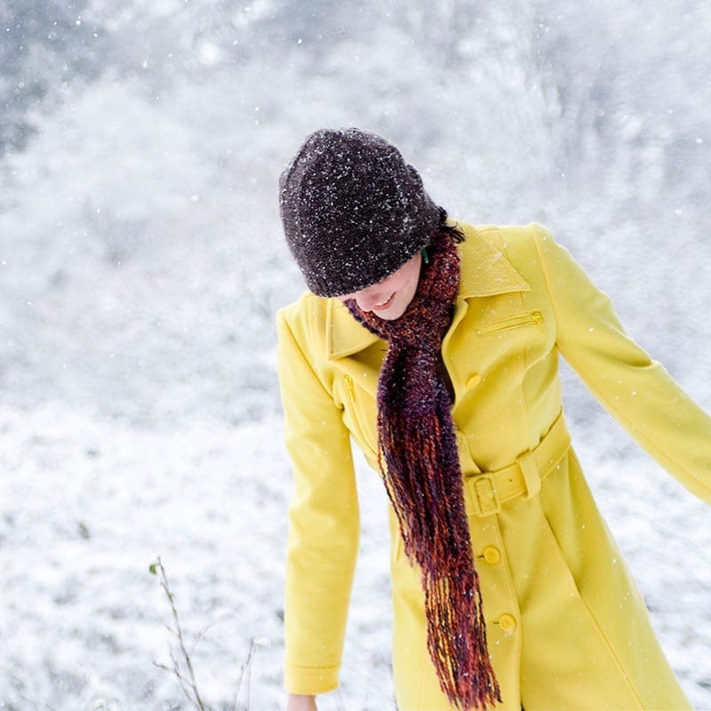 Woman in a yellow jacket walking through snow