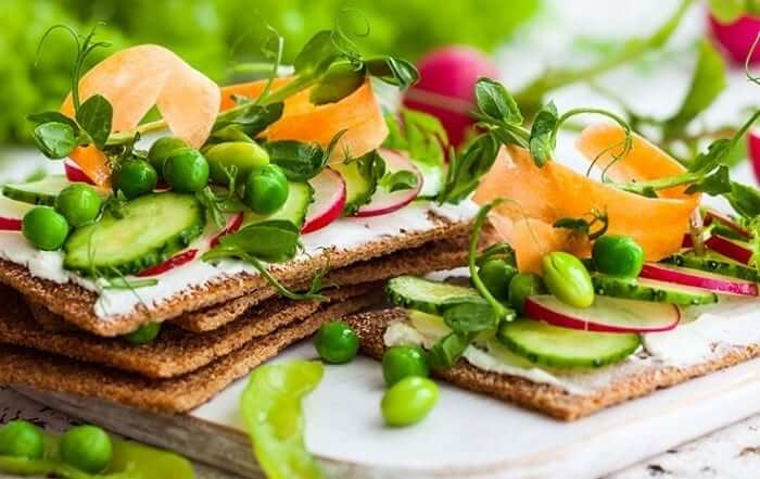 Vegetables and cheese spread on crackers