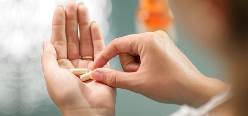 Woman taking supplement pill