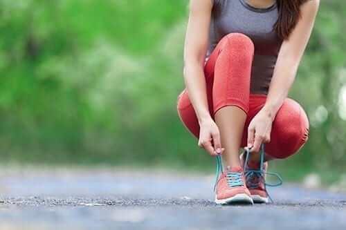 Woman Tying Shoe While Exercising
