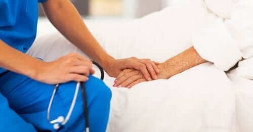 Medical professional holding patients hand