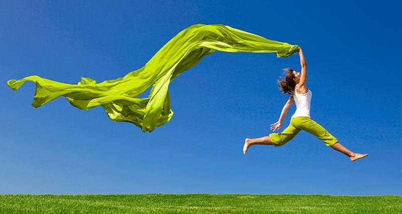 Woman with green sheet leaping